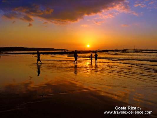 tourists watching the sunset at tamarindo beach