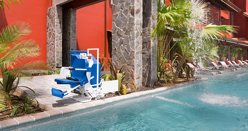 disabled-friendly swimming pool surrounded by vegetation which gives more privacy
