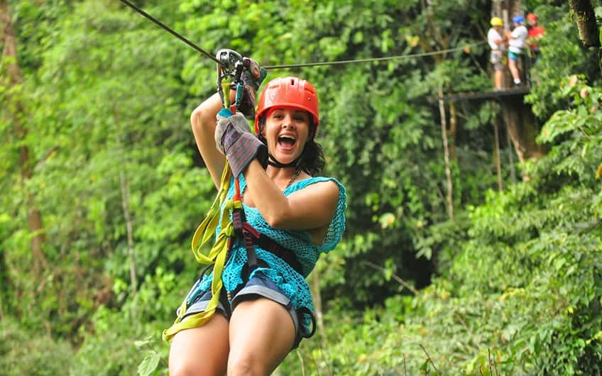 A girl having fun at a canopy tour inside the Manuel Antonio rain forrest