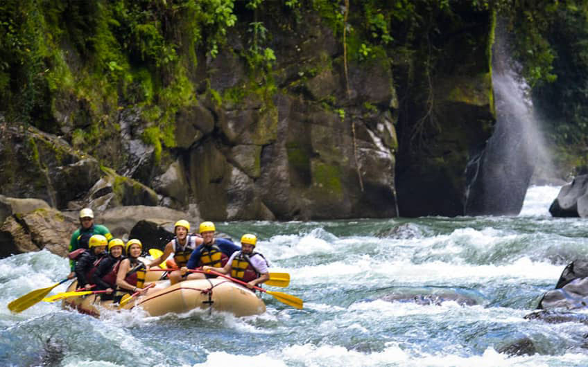 A group of people enjoying the adrenaline of the white water rafting tour on the Pacuare River.