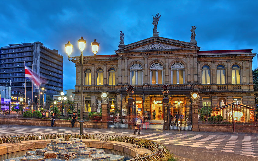 The facade of the National Theater of Costa Rica during an afternoon that shows the daily movement of people through the capital city.