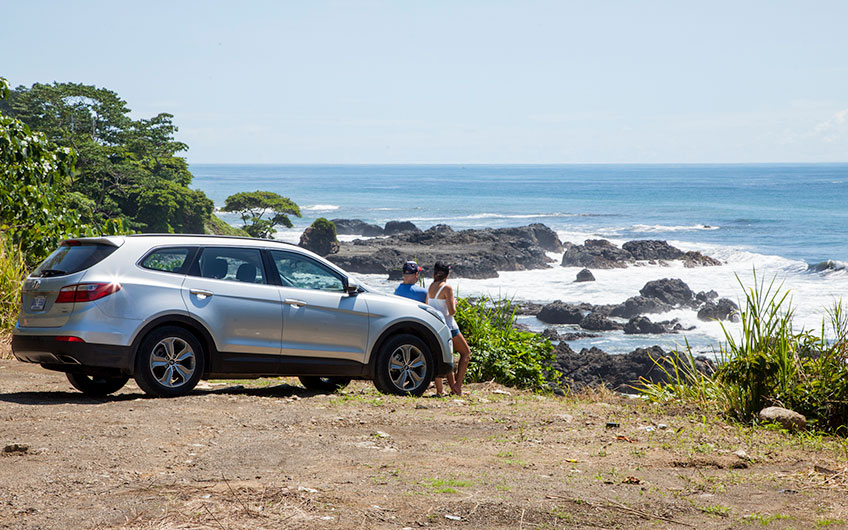 A couple lean back in their rental car while enjoying the ocean view on a sunny morning.