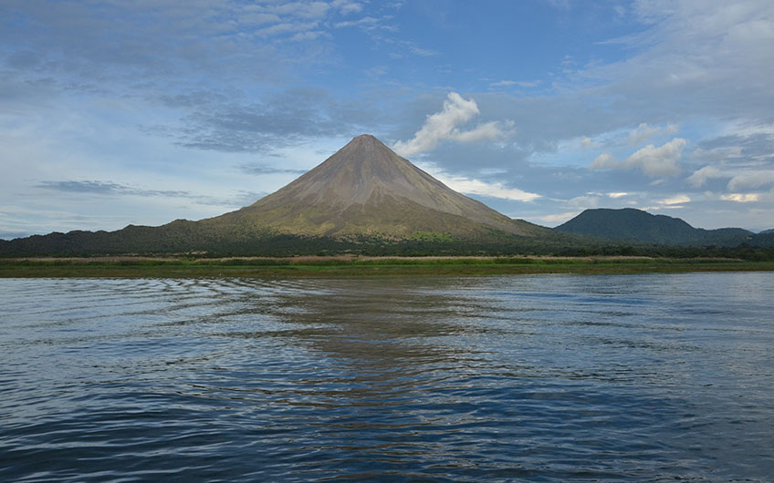 The imposing Arenal volcano and part of the Arenal lake subtly portrayed during a calm morning.