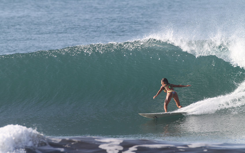A surfer swings nimbly in the warm ocean waves at Tamarindo Beach.