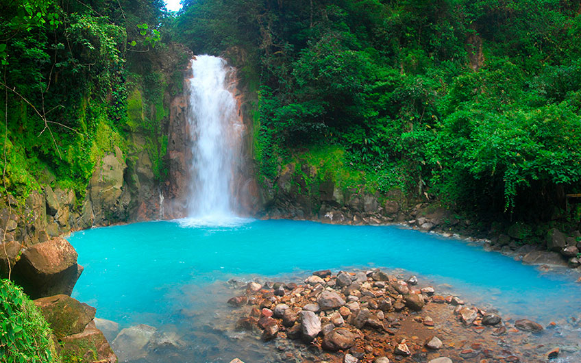 The powerful waterfall and the natural pool of turquoise water are surrounded by the greenery of the landscape and offer an unbeatable view of the Tenorio Volcano National Park, in Guanacaste.