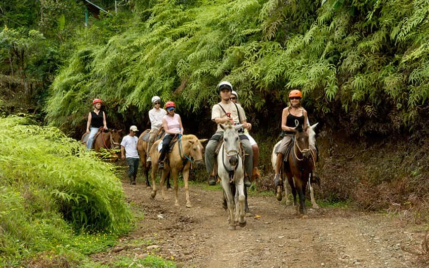 six people horseback riding inside the rainforest at Manuel Antonio National Park