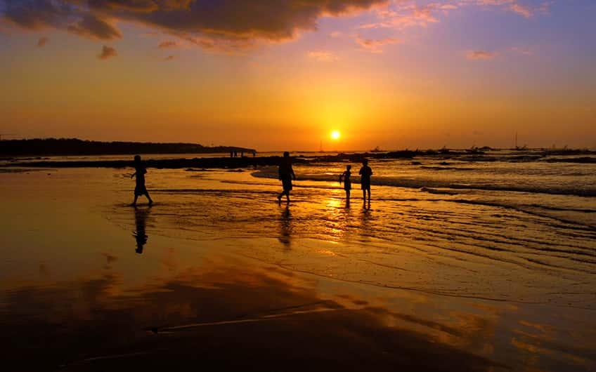 People on Tamarindo beach enjoying a beautiful sunset.
