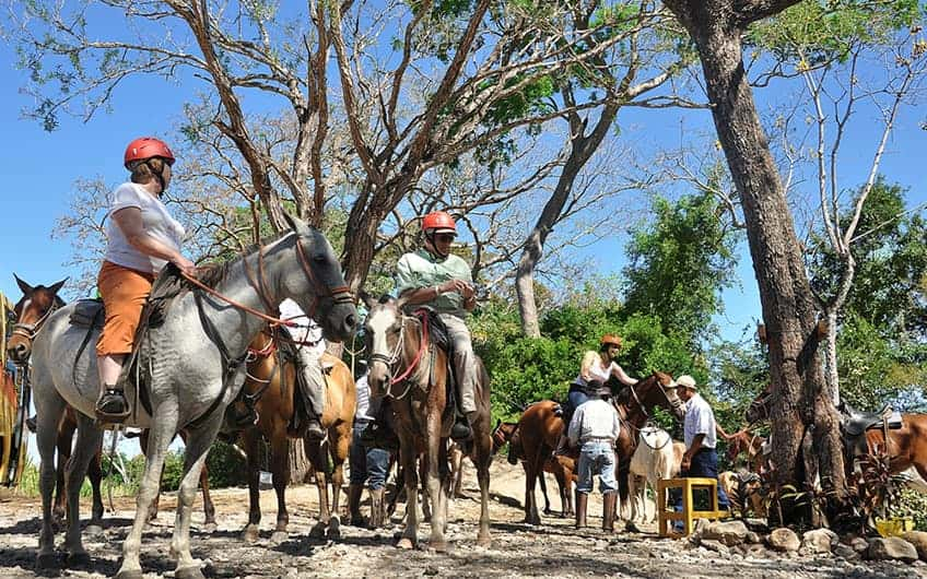 A group of tourists ready to start their horseback riding tour in Tamarindo.