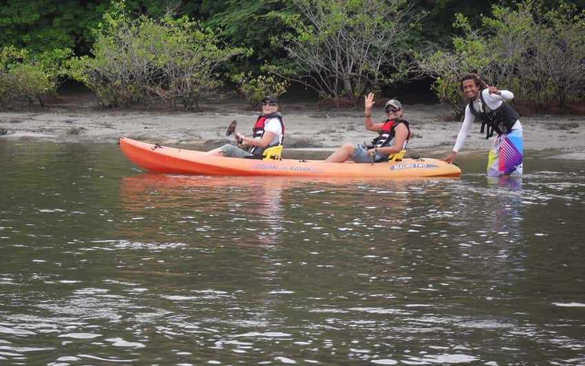 A couple of tourists posing for a picture with their tour guide while kayaking.