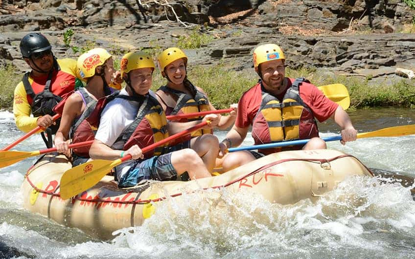 A group of people enjoying a white water rafting tour in the river.