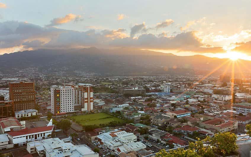 Das Wetter in San Jose Costa Rica kann je nach Tageszeit variieren. Auf dem Bild ist der Sonnenuntergang der Stadt von oben zu sehen.