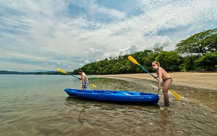 A couple is ready to have some fun while sea kayaking, which is one of the preferred things to do in Guanacaste.